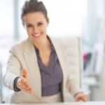 Closeup on happy business woman stretching hand for handshake in office