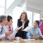 five businesspeople are discussing something on a meeting