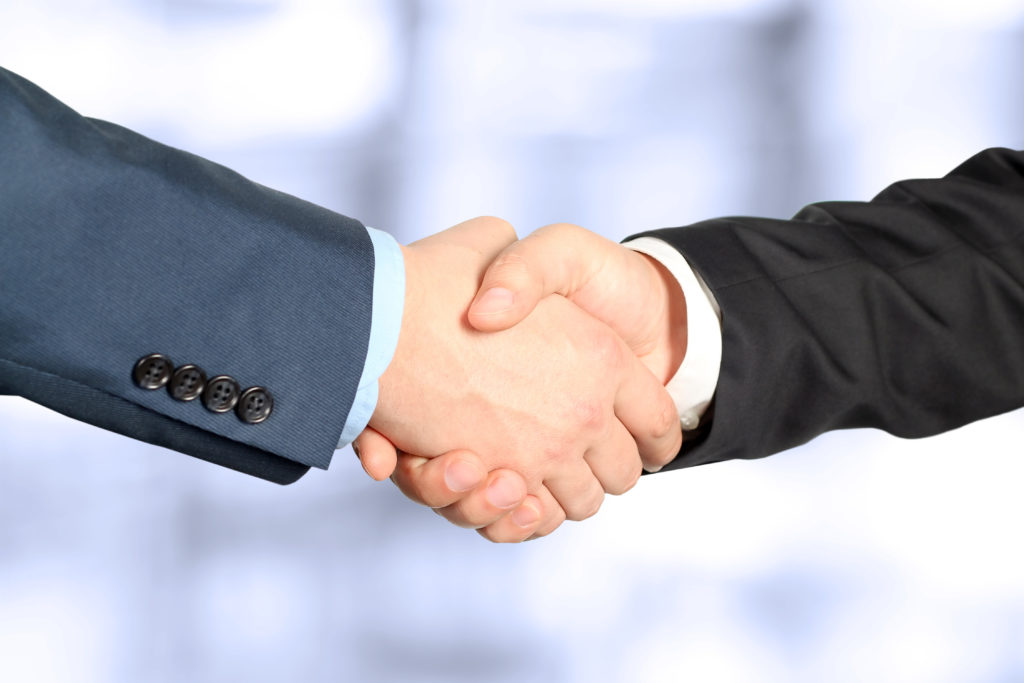 Close-up image of a firm handshake between colleagues in office. Interview